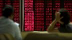 Zwei Menschen sitzen vor einer Wand mit digitalen Börsenkursen.