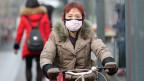 Eine chinesische Radfahrerin mit Maske in der Nähe des geschlossenen Huanan Seafood Wholesale Market, der mit Fällen eines neuen Coronavirus-Stammes in Verbindung gebracht wurde.