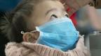 Kind mit Schutzmaske.