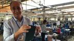 In einer Fabrik ausserhalb der Stadt Siem Reap in Kambodscha sitzen Frauen an ihren Nähmaschinen. Im Vordergrund der Geschäftsführer Arjen Laan.