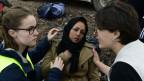 NGO-Mitglieder helfen einer Flüchtlingsfrau auf Lesbos.