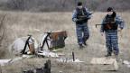 Bewaffnete stehen neben Wrackteilen der abgeschossenen MH17-Maschine.