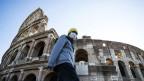 Ein einsamer Tourist vor dem Kolosseum in Rom.