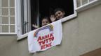 Zwei Kinder in Rom zeigen mit einem Plakat, dass es ihnen trotz Corona-Notstand gut geht.