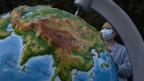 Eine Frau mit einer Gesichtsmaske betrachtet einen Globus, der Wuhan zeigt, in der zentralchinesischen Provinz Hubei, China.