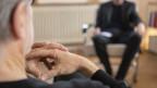 Ein Psychotherapeut, rechts, therapiert einen Klienten in seiner Praxis.