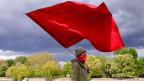 Eine Frau mit einer roten Fahne nimmt an einer Protestaktion am 1. Mai 2020 im Bezirk Kreuzberg in Berlin, Deutschland, teil.