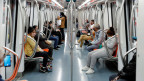 Menschen mit Schutzmasken in einer Metro in Rom.