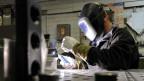 Ein Mitarbeiter eines metallverarbeitenden Betriebes beim Schweissen.