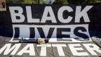 Ein schwarzer Mann liegt auf einer Black Lives Matter-Fahne in den USA.