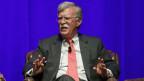 John Bolton, der ehemalige Sicherheitsberater von Trump, sitzt auf einem Podium in einem Sessel und spricht zum Publikum.