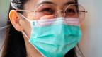 Eine junge Frau schützt sich mit einer Gesichtsmaske.