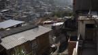 Ein Mann in Schutzanzug desinfiziert ein Favela in Rio de Janeiro.