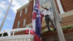 Ein Mann entfernt vor dem Rathaus in Tupelo die bisherige Staatsflagge von Mississippi.