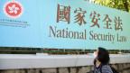 Eine Frau geht am 30. Juni 2020 in Hongkong an einem Werbebanner für das nationale Sicherheitsgesetz für Hongkong vorbei.