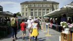 Kunden besuchen den wöchentlichen Lebensmittel- und Blumenmarkt auf dem Bundesplatz in Bern.
