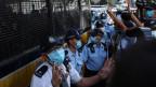 Polizisten halten Wache, während der pro-demokratische Protestler Tong Ying-kit, 23, das Gericht verlässt.