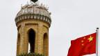 Chinesische Flagge vor dem Minarett der Id Kah-Moschee in Kaxgar, Xinjiang. In beiden Ländern nehmen Konflikte entlang ethnischer und religiöser Linien zu.