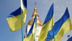 Ukrainische Flaggen vor der St. Michaelis-Kathedrale mit goldener Kuppel in Kiew.
