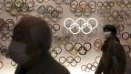 Zwei Personen mit Schutzmasken gehen an einer Wand voller Logos der Olympischen Spiele 2020 vorbei.