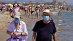 Zwei Personen mit Schutzmasken gehen einem Strand in der Nähe von Valencia entlang.