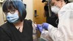 Eine Krankenschwester gibt einer Freiwilligen im Rahmen einer Studie einen Impfstoff gegen Covid-19.
