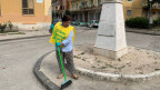 IEine Freiwillige aus Acerra fegt an einem Sonntagmorgen den Platz vor dem Bahnhof.