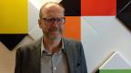 Christoph Doswald vor Max-Bill- Wandrelief im SRF-Radiostudio Zürich.