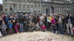 Passanten erfreuen sich an den acht Millionen 5-Rappen-Stücken im Wert von 400'000 Schweizer Franken und mit einem Gewicht von 15 Tonnen auf dem Bundesplatz, am Freitag, 4. Oktober 2013, in Bern. Diese Aktion fand anlässlich der Unterschriftenübergabe der Initiative «Bedingungsloses Grundeinkommen» statt.