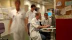 Zwei Krankenpfleger suchen Patientendossiers in der Notfallaufnahme des Universitätsspitals in Genf.