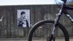 Ein Graffiti Mani Matters auf der Mauer einer Velo- und Fussgängerbrücke über die Autobahn im Bremgartenwald bei Bern.