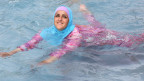 Türkisches Mädchen beim Schwimmen im Burkini. Symbolbild.