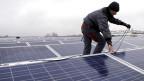 Ein Arbeiter montiert auf einem Dach Solarmodule. Symbolbild.