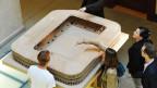 Personen schauen sich das Modell «Hypodrom» des neuen Zürcher Stadions an, am Donnerstag, 4. Juli 2013, anlässlich einer Ausstellungseröffnung in Zürich. Nach heutigem Stand der Projektierung werden die anvisierten Zielkosten von 150 Millionen Franken eingehalten.