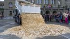 Ein Lastwagen kippt eine Ladung mit acht Millionen 5-Rappen-Stücken im Wert von 400'000 Schweizer Franken und mit einem Gewicht von 15 Tonnen auf den Bundesplatz, am Freitag, 4. Oktober 2013, in Bern. Diese Aktion fand anlässlich der Unterschriftenübergabe der Initiative «Bedingungsloses Grundeinkommen» statt.