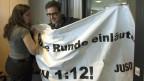 JUSO Präsident David Roth versucht, mit einem Plakat zur 1:12 Initiative «Für gerechte Löhne» das Abstimmungslokal von Economiesuisse zu stören am, 3. März 2013, in Bern.