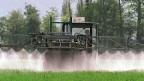 Ein Landwirt verprüht Pestizide auf einem Feld; diese landen unweigerlich in Bächen oder Seen.