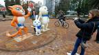 Eine Touristine fotografiert die drei Maskottchen der Olympischen Spiele.