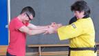Ohne Krücken kann Rinor nicht gehen. Für den Selbstverteidigungs-Kurs hat der 16-Jährige sie zur Seite gelegt. Hier boxt er gegen Kursleiterin Karin Grunder.
