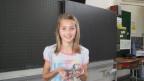 Die 12jährige hörbehinderte Sonja zeigt ihr Hörgerät.