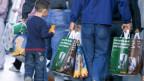 Eine Familie mit mehreren Einkaufstüten beladen. Symbolbild