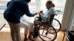 Eine Pflegerin unterhält sich mit einer gehbehinderten Bewohnerin im Pflegeheim Belvoir in Bern. Archivbild.