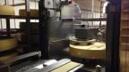 Ein Roboter schmiert die Käselaibe mit Salzwasser.