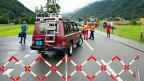 Feuerwehrleute, Polizisten und Medienschaffende bei einer abgesperrten Strasse in der Nähe des Unfallortes bei einem unbewachten Bahnübergang in Wolfenschiessen NW.
