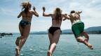 Junge Menschen kühlen sich mit einem Sprung in den Zürichsee ab. Symbolbild.