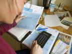Eine junge Frau bei der Berechnung ihrer Krankenversicherungskosten.