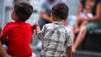 Kinder von Asylbewerberfamilien sitzen vor dem Empfangs- und Verfahrenszentrum Chiasso.