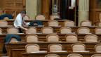 An zwei von drei Pulten im Nationalratssaal sitzen Männer.