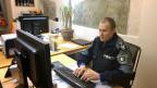 Roger Schneider von der Regionalpolizei Zurzibiet an seinem Arbeitsplatz vor dem Computer.
