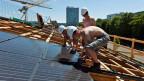 Bauarbeiter montieren eine Solaranlage. Symbolbild.